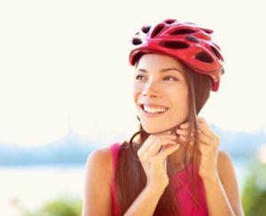 mature women doing up a red bike helmet