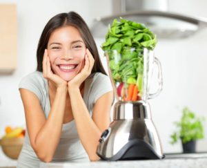 your women next to blender with veggies inside