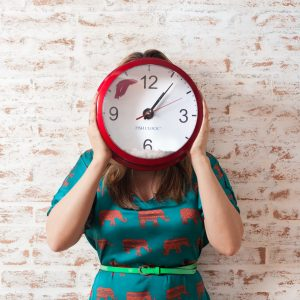 women standing holding clock over face