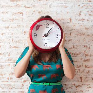 women standing holding clock over face